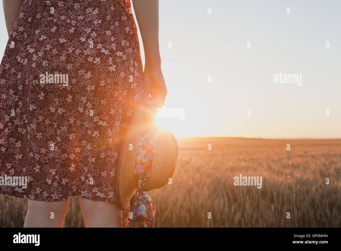 Despedida de espera ou conceito, pôr-do-sol de verão, mulher mão segurando hat Imagens de Stock