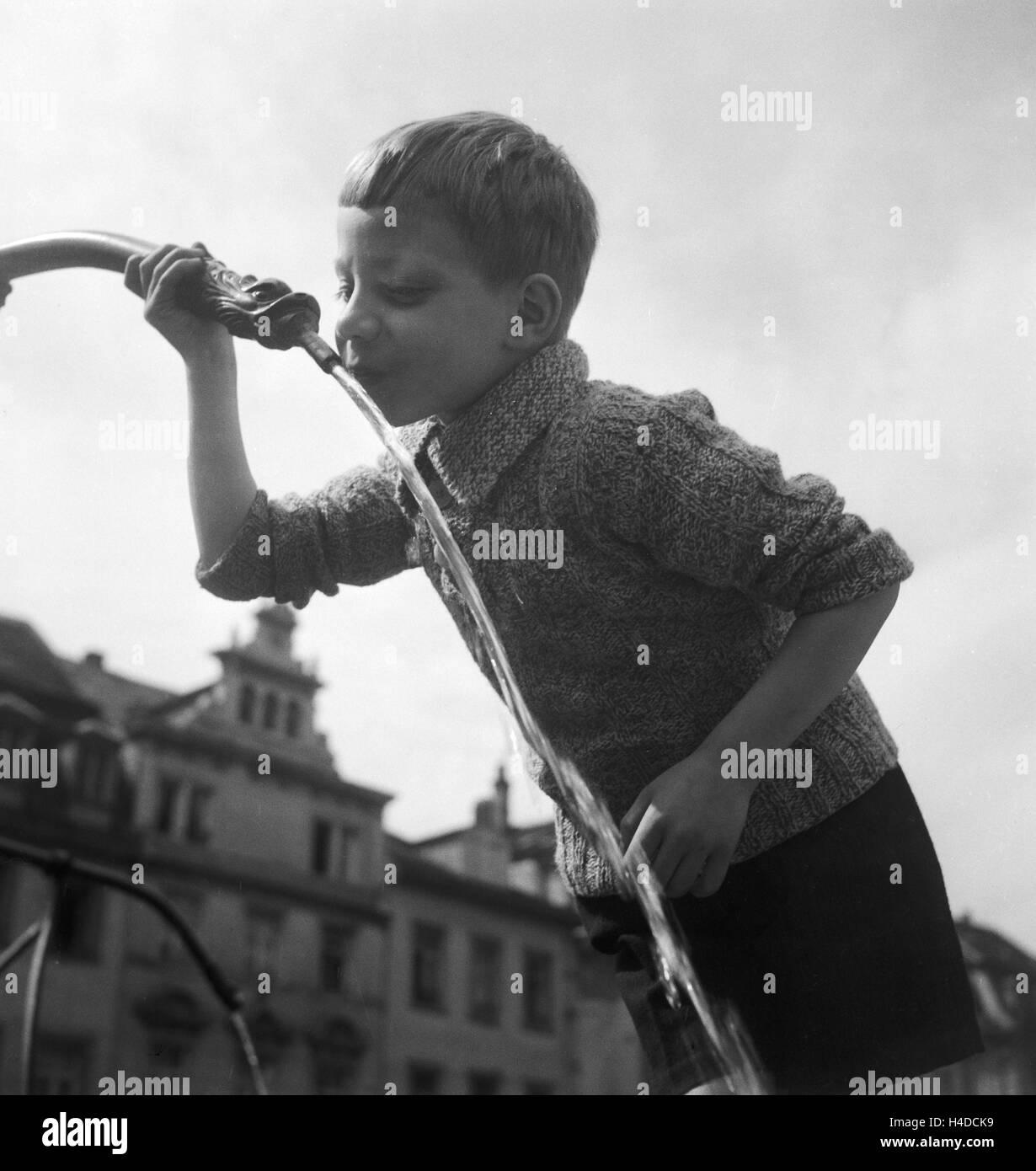 Ein Junge trinkt Wasser aus einem Brunnen, Deutschland er Jahre 1930. Um rapaz de água potável a partir Imagens de Stock