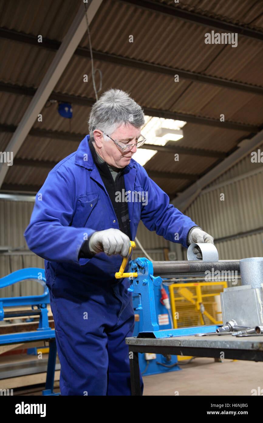 Rolos de um trabalhador de uma tira de metal em um prédio da oficina de fabricação de seções Imagens de Stock