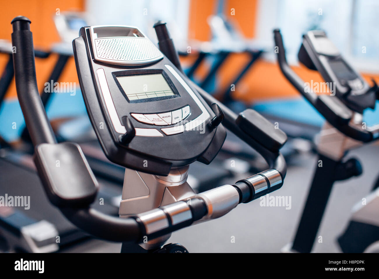 Aeróbica spinning bicicletas de exercício sala de ginástica com muitos em uma linha Imagens de Stock