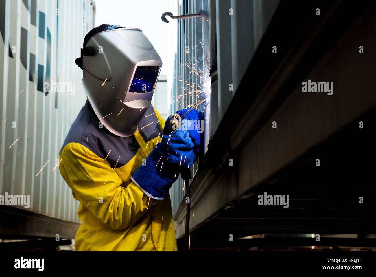 Trabalhador da indústria com soldagem de chapas de aço para reparar estruturas recipiente fabrico oficina. Imagens de Stock