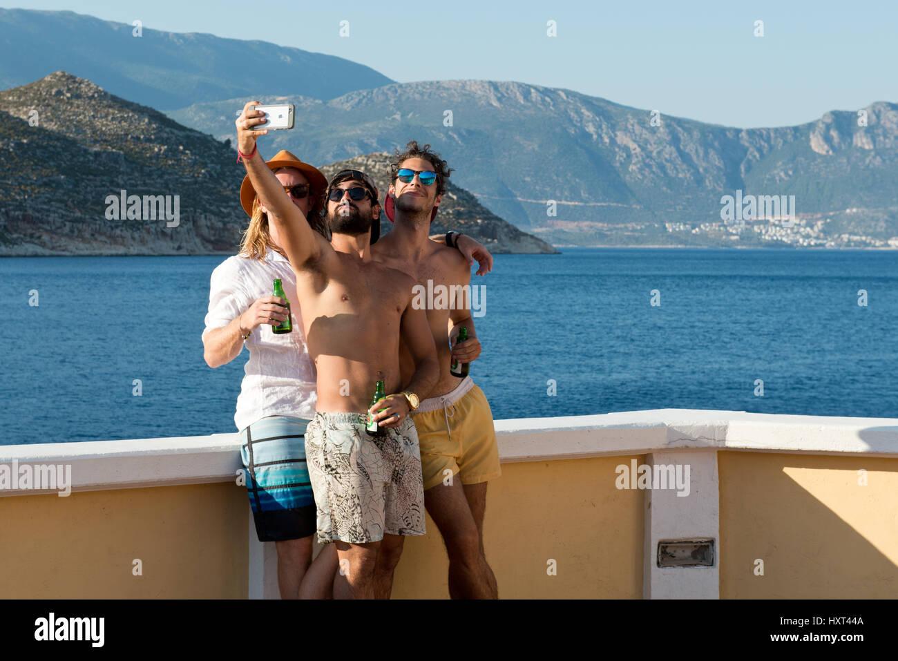 Drei junge Männer em Badehosen mit Flaschen machen ein Selfie mit Meer und Küste im Hintergrund, Insel Imagens de Stock