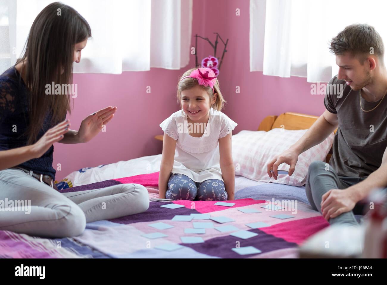 Mãe e filha jogando na cama. Conceito de diversão em família Imagens de Stock
