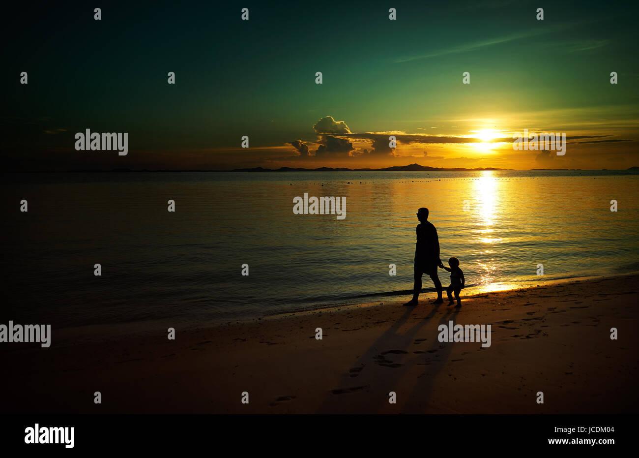 Pai e filho andando na Sunset Beach , Silhouette shot e o tom de imagem . Imagens de Stock