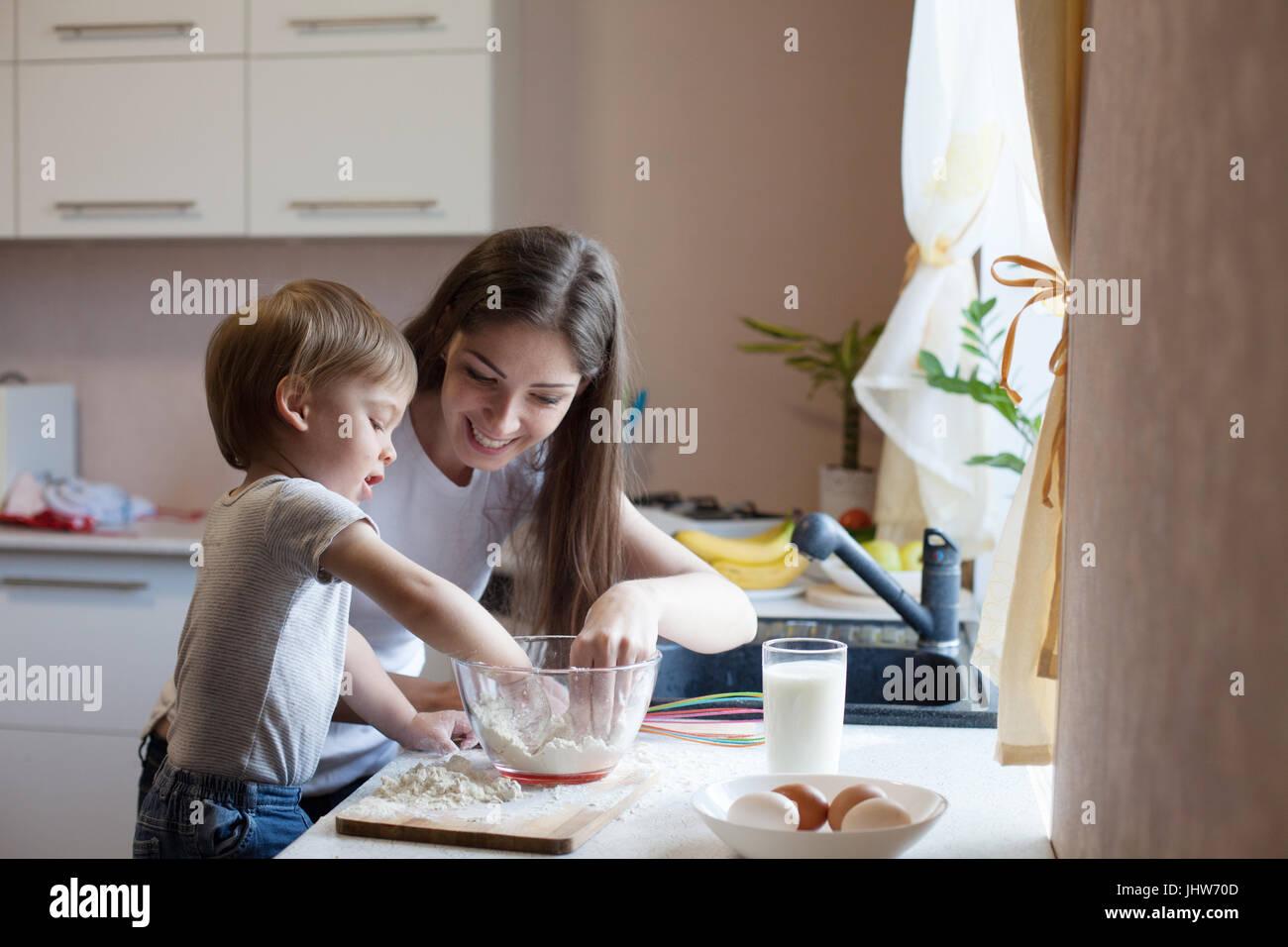 A mãe e o filho preparar pizza com farinha Imagens de Stock