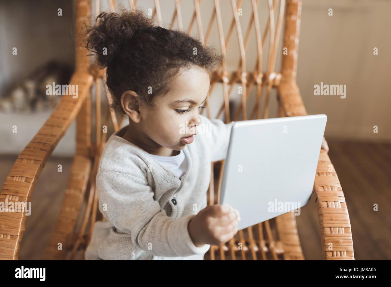 Adorável african american menina usando tablet digital e sentado na cadeira de balanço em casa Imagens de Stock