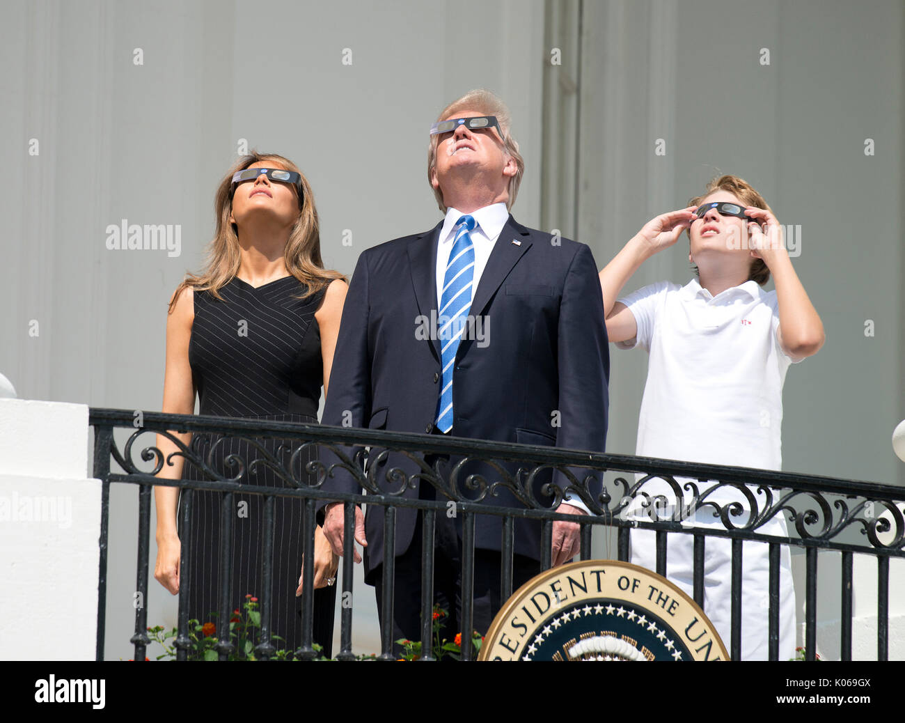 Presidente dos Estados Unidos Donald J. Trump, centro, acompanhado de primeira-dama Melania Trump, para a esquerda e para a direita, Barron Trump, olhar o eclipse parcial do sol a partir da varanda do quarto azul da Casa Branca em Washington DC na segunda-feira, 21 de Agosto de 2017. Crédito: Ron Sachs / CNP - SEM FIOS - Foto: Ron Sachs/Consolidado/DPA Imagens de Stock