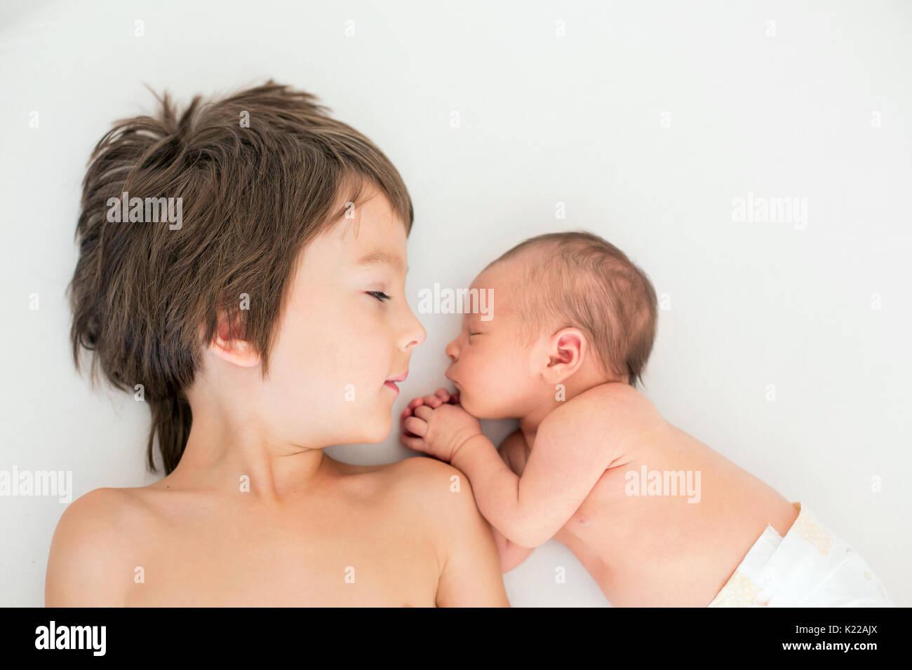 Belo boy, abraçando com ternura e cuidados que o seu bebê recém-nascido irmão em casa. O amor Imagens de Stock