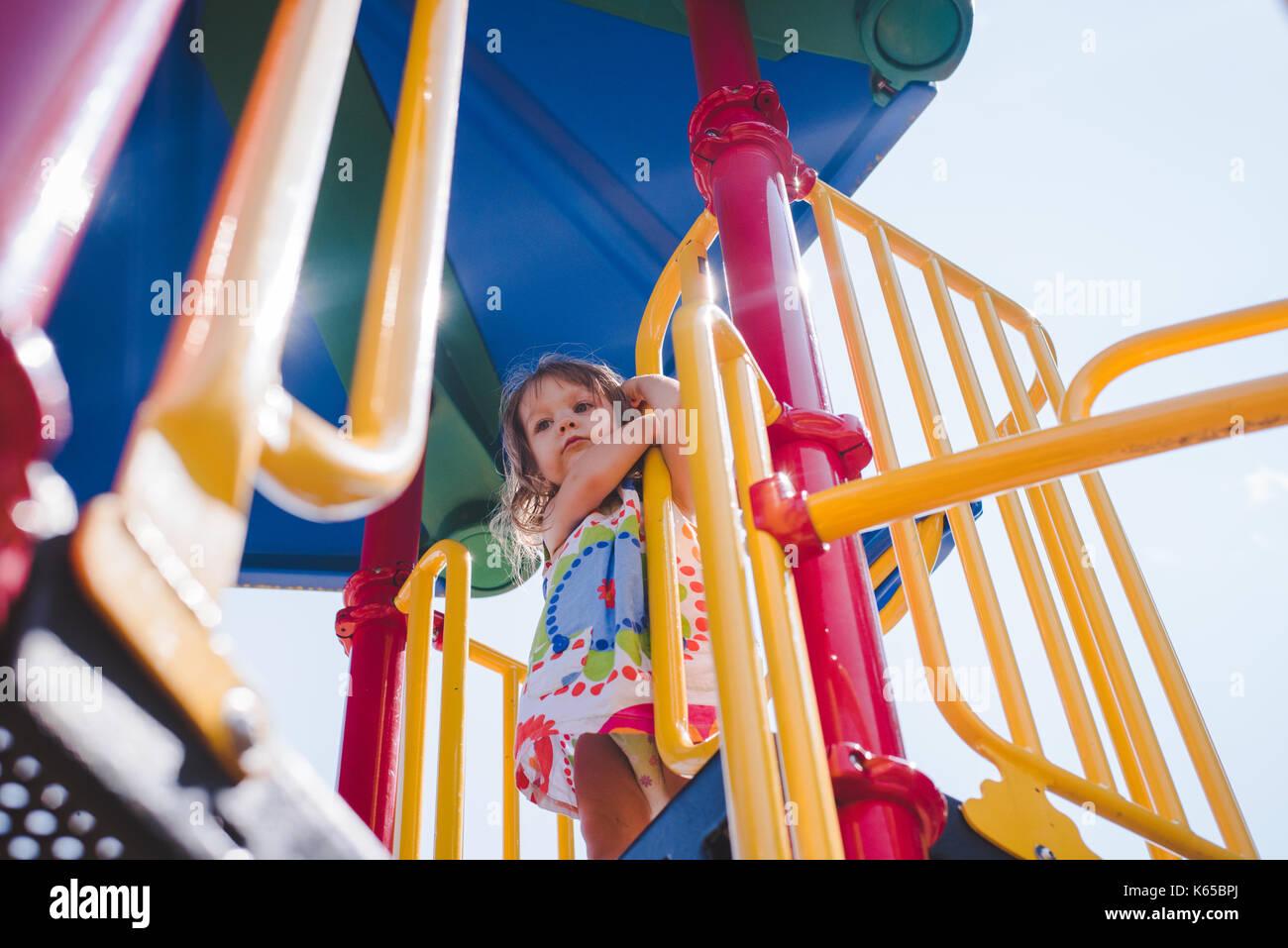Uma criança rapariga desempenha em equipamentos de playground em um dia ensolarado. Imagens de Stock