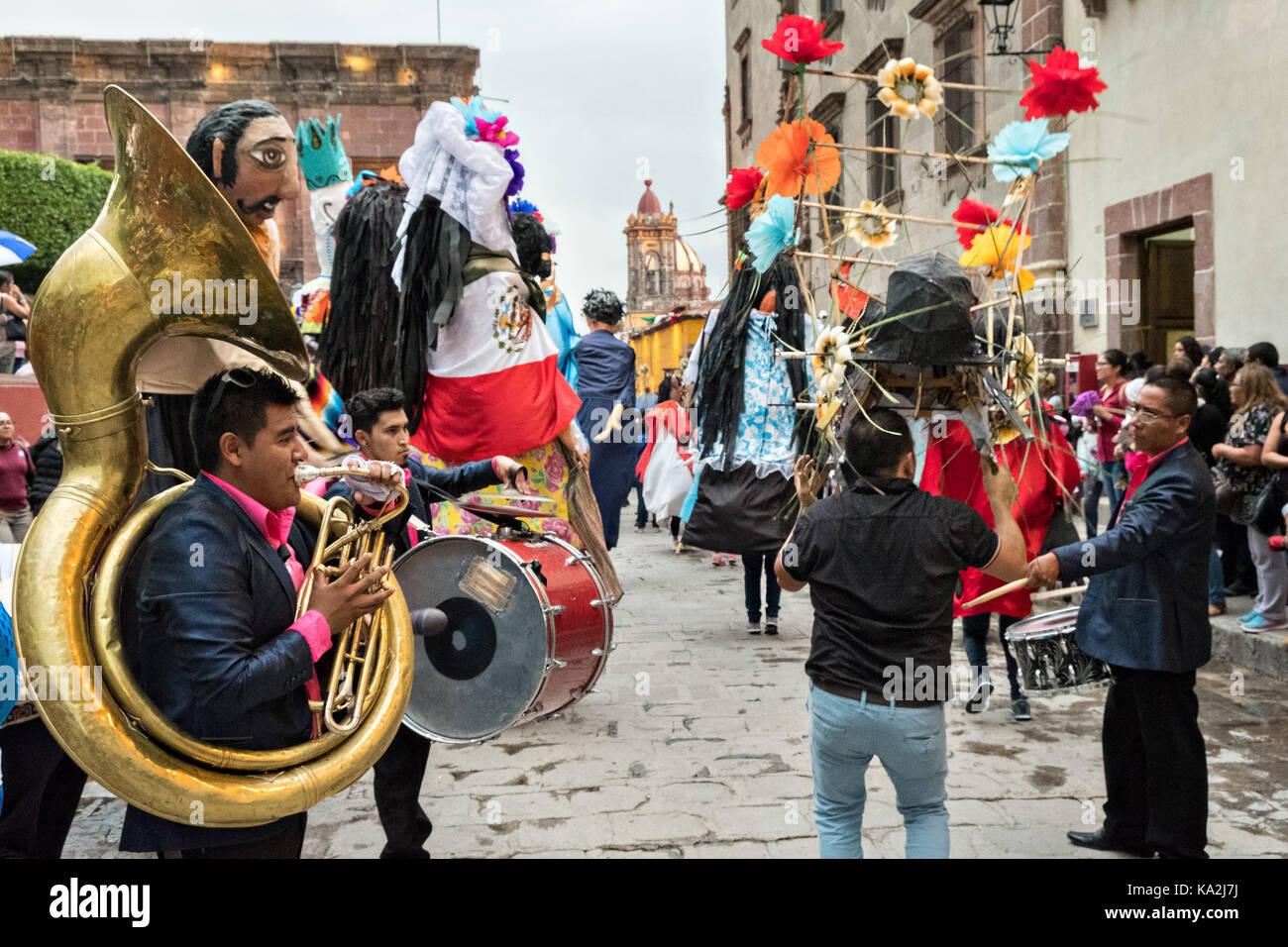 Uma banda marchando segue um desfile de papel machê marionetas gigantes chamados mojigangas em uma procissão Imagens de Stock