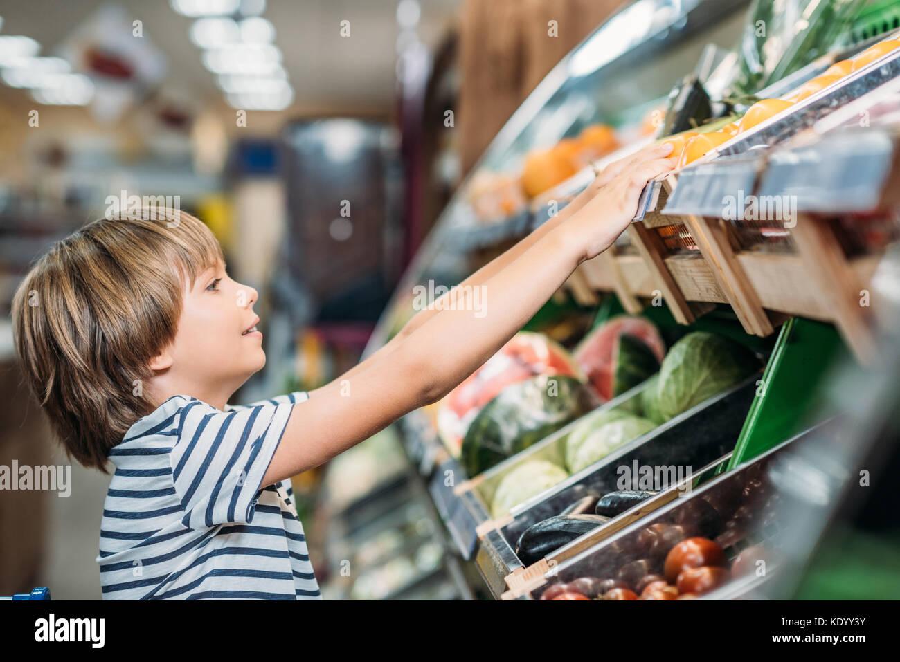 Boy escolhendo alimentos na mercearia Foto de Stock