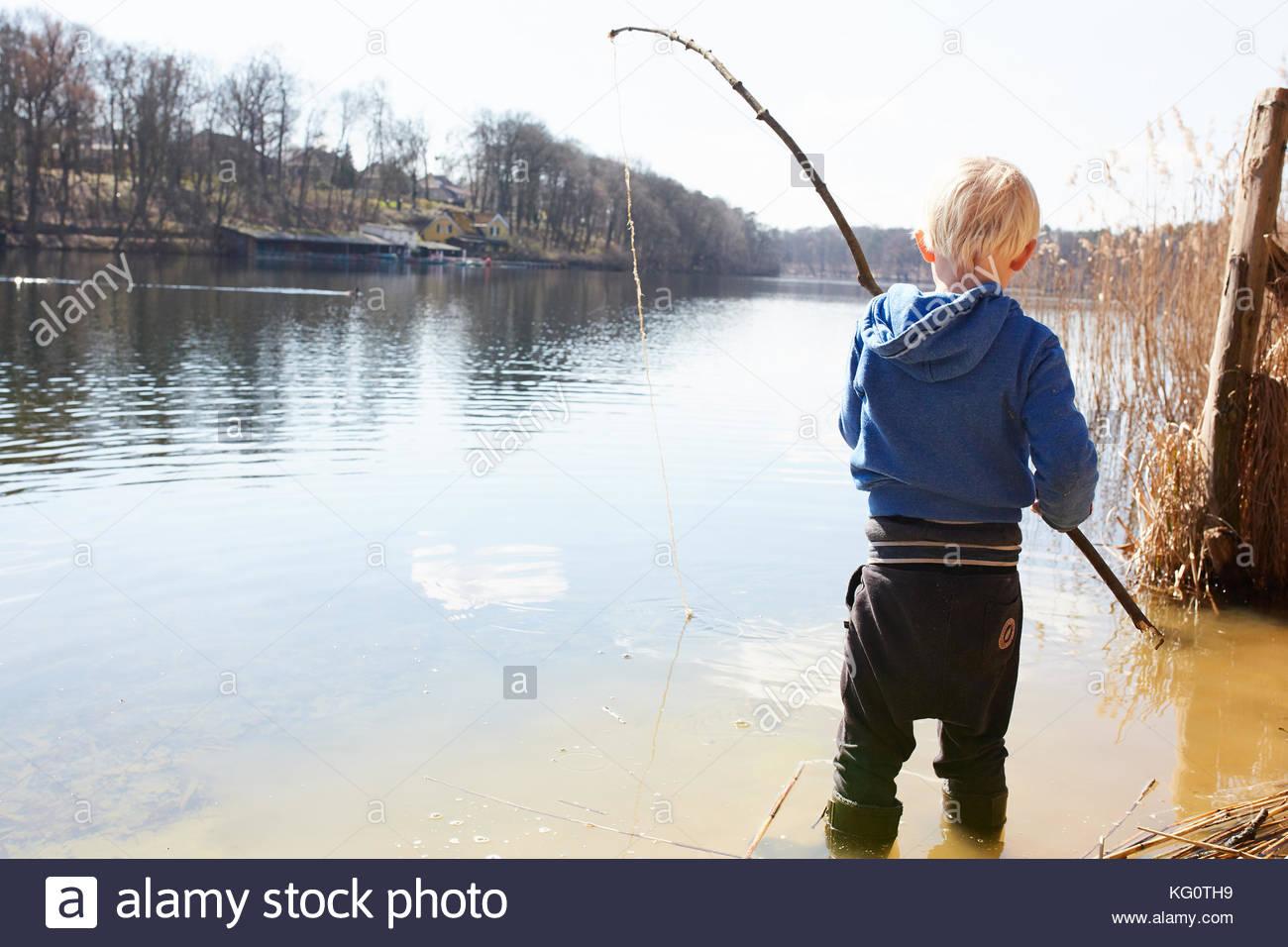 Criança brincando por um lago Imagens de Stock