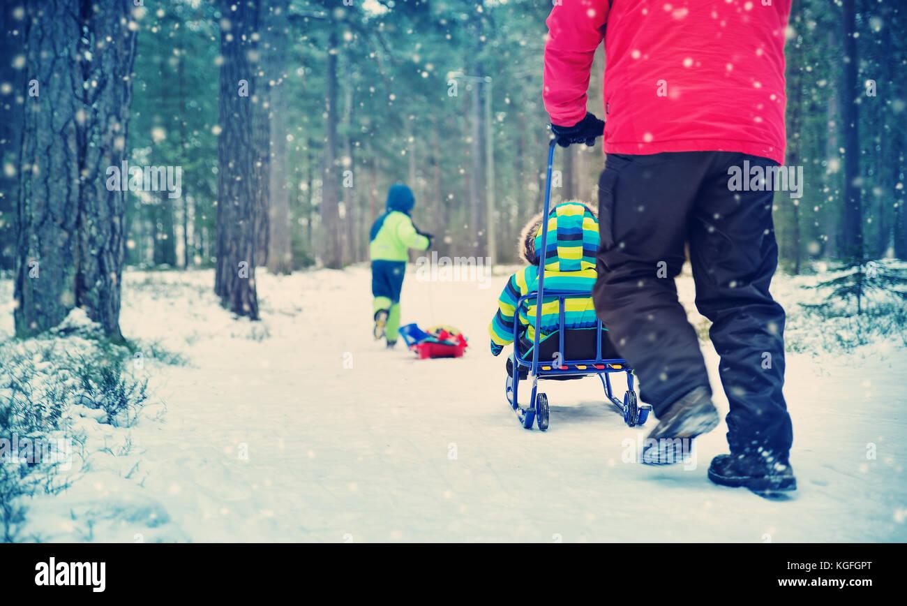 Pai com filhos andando na neve Imagens de Stock