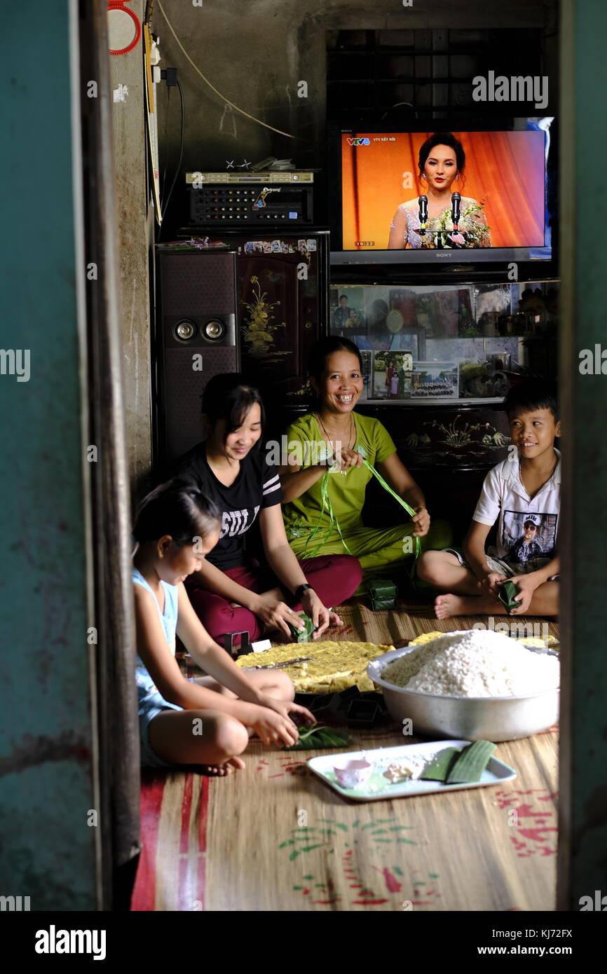 Família, preparando panquecas de arroz vietnamita para mercado em casa em uma vila local Imagens de Stock