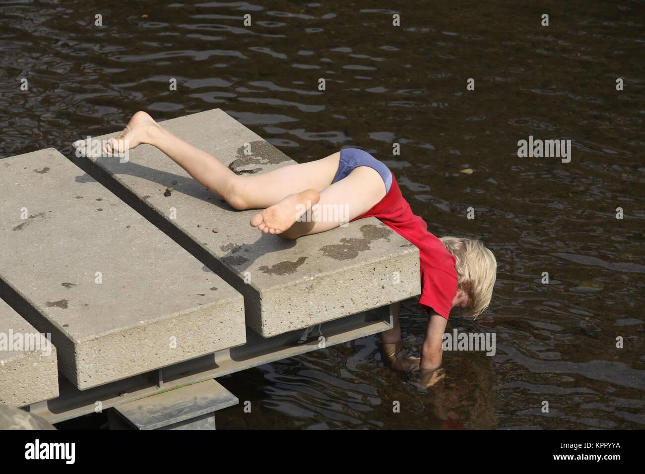 Germnay, Bergisches Land, Muengsten, menino deitado em uma doca no Rio Wupper. Deutschland, Bergisches Land, Muengsten, Imagens de Stock