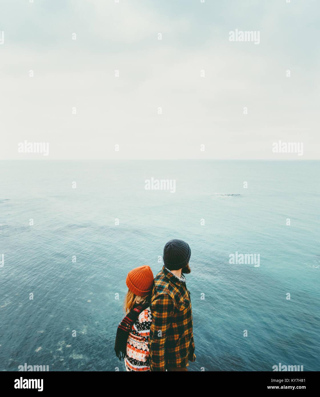 Casal que se ama o homem e a mulher de volta para trás em pé acima do mar, viajando juntos emoções Imagens de Stock