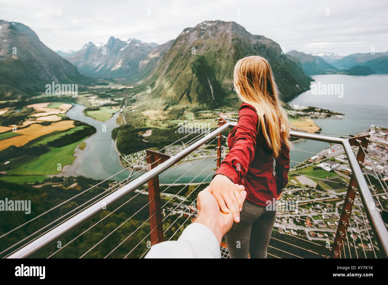 Casal homem e mulher seguem de mãos dadas na Noruega montanhas Amor e viaje feliz emoções conceito Imagens de Stock