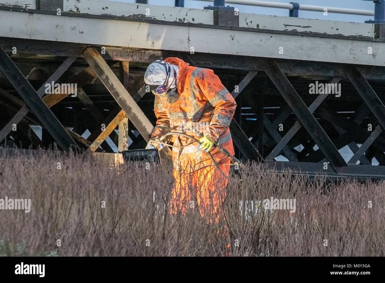 Uma metalúrgica de soldar as escoras de ferro durante os trabalhos de renovação no Cais de Southport Imagens de Stock