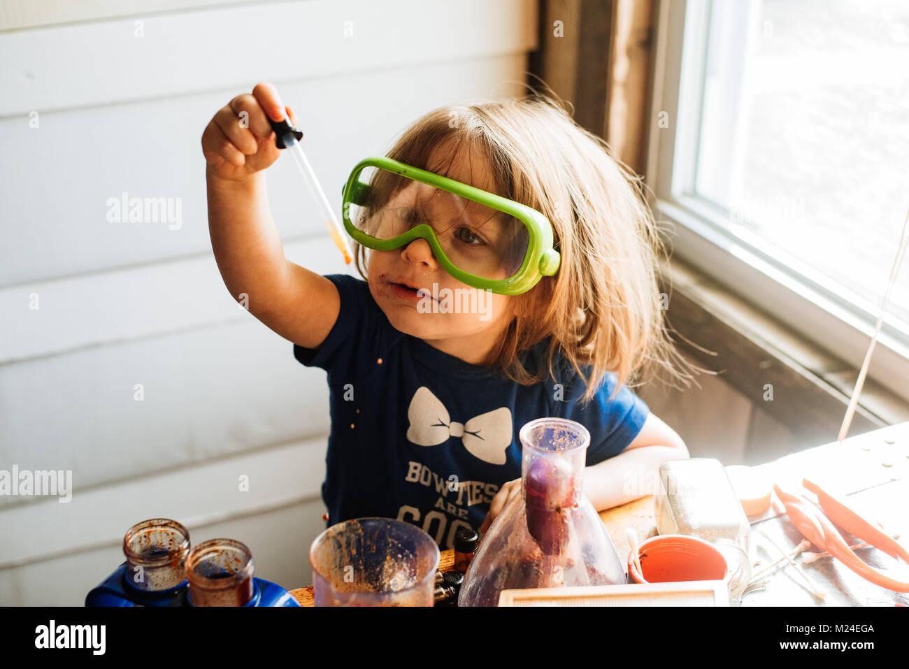 Uma criança de 3 anos de idade menina trabalha com equipamento de experimento de ciência Imagens de Stock