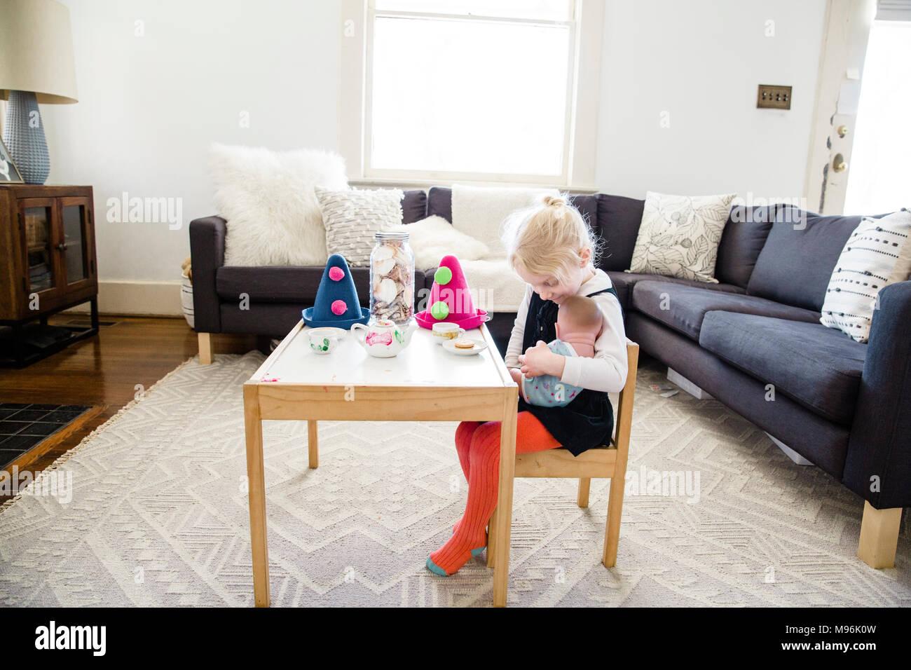 Menina sentada na cadeira junto à mesa com chapéus de festa Imagens de Stock