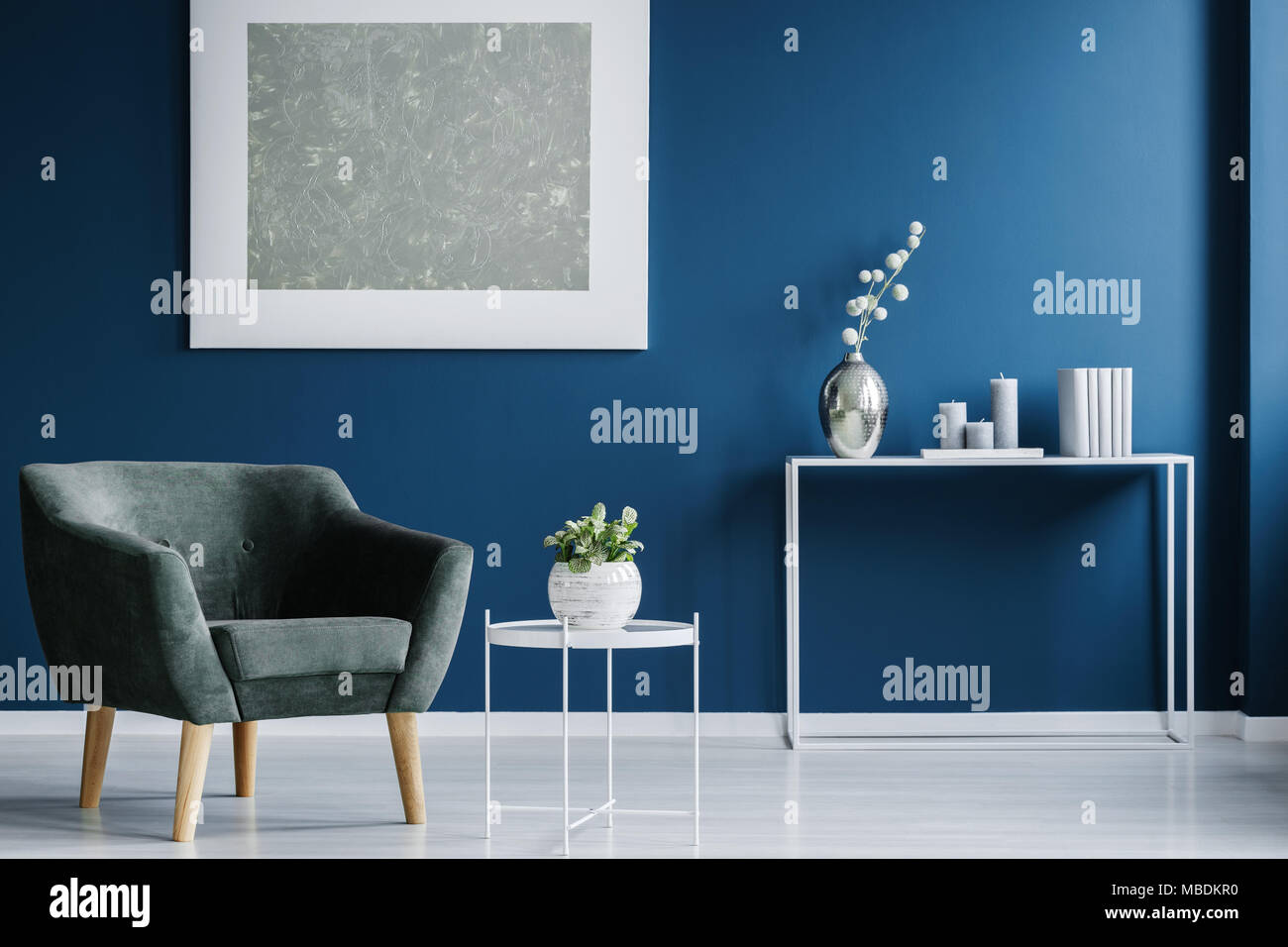 Green armchair against the wall with silver painting in navy ...