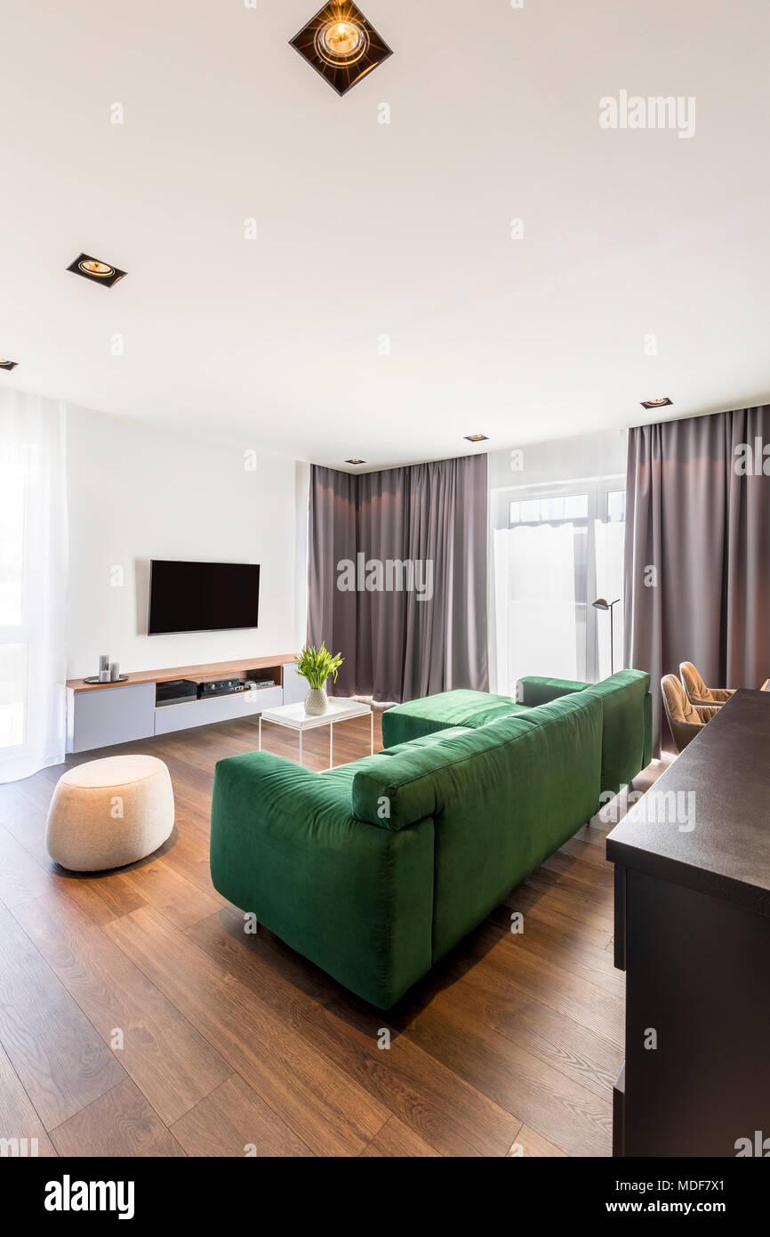 Spacious living room interior with green corner sofa, wooden ...