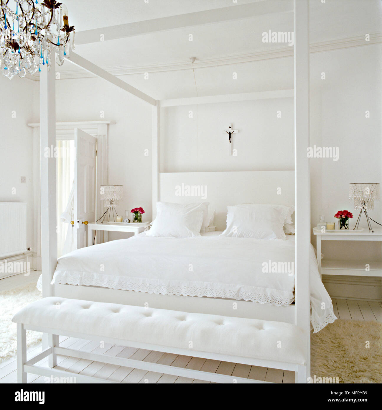 a modern minimalist white bedroom with double four poster bed with upholstered headboard bench seat bedside tables