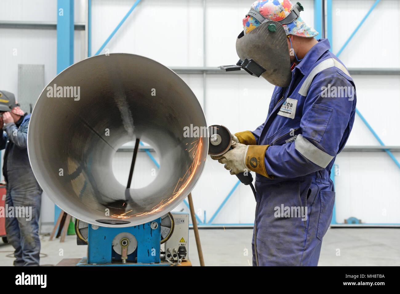 O homem corte de grandes tubo com esmeril no workshop de engenharia Imagens de Stock