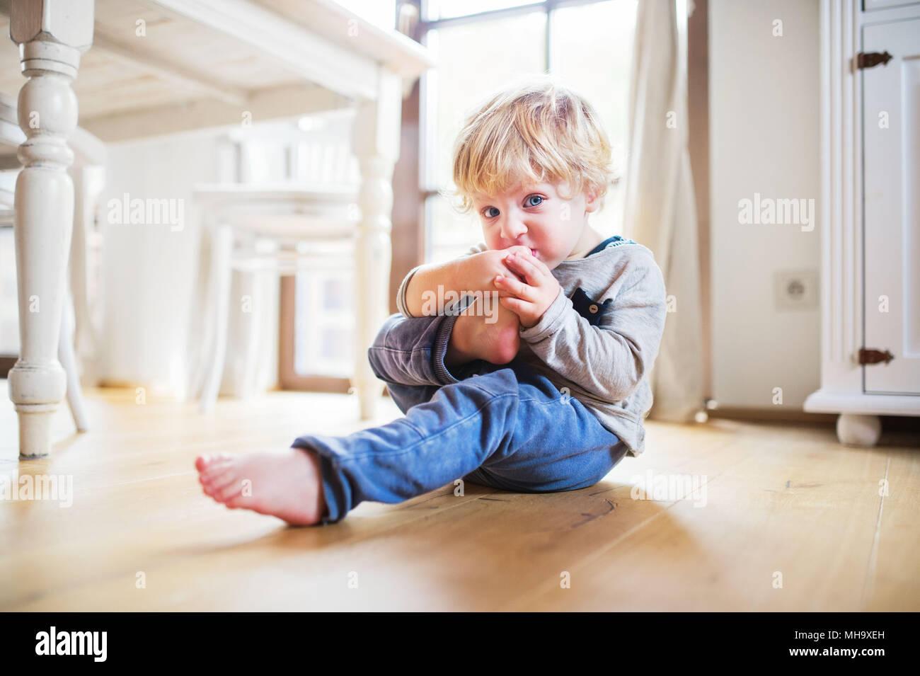 Uma criança menino sentado no chão em casa. Imagens de Stock