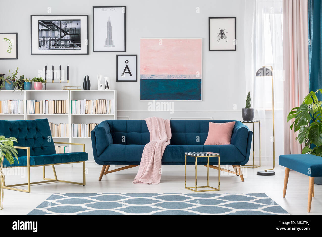 Lamp next to navy blue couch against the wall with pink ...