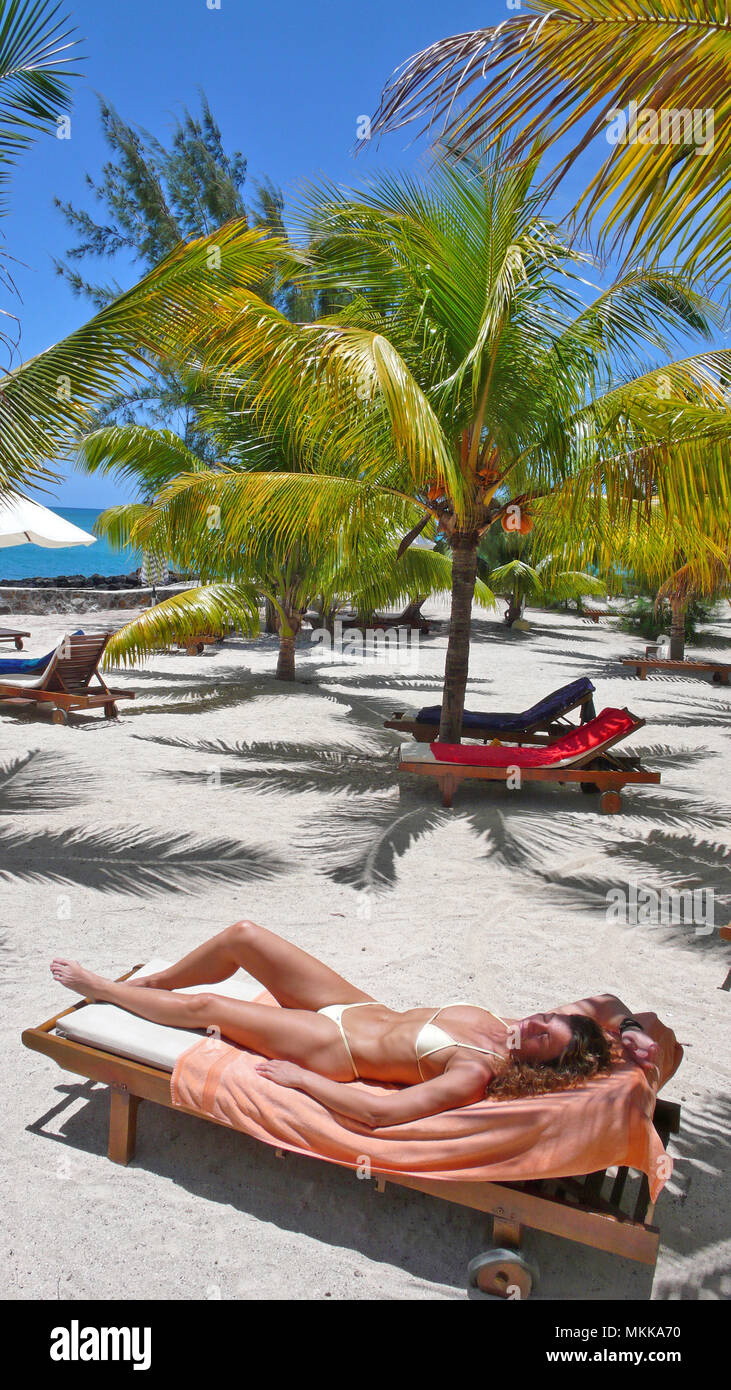 Sonnt junge Frau sich unter Palmen am Meer | jovem sob palmeiras banhos de sol numa espreguiçadeira na praia Imagens de Stock