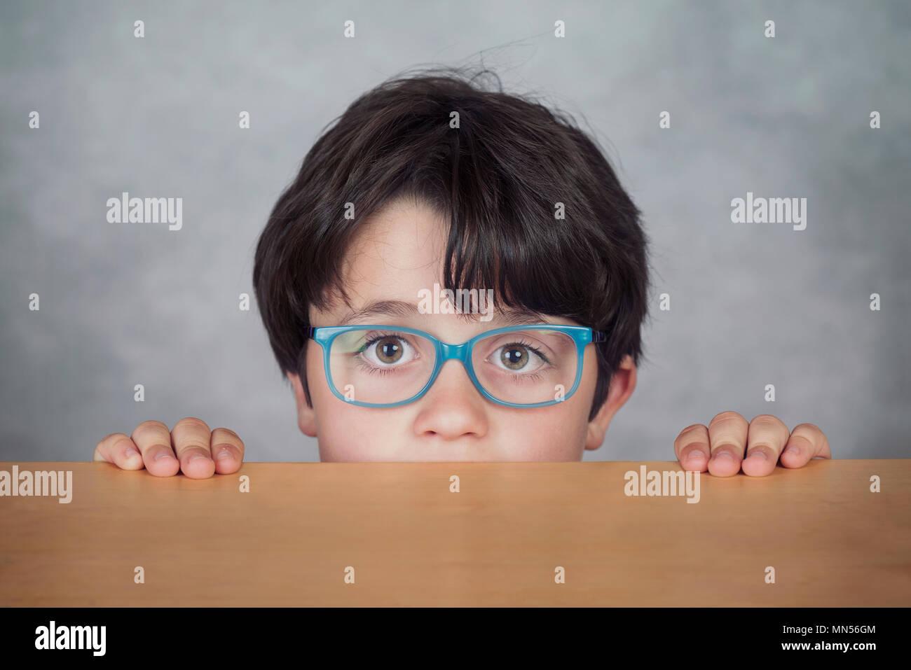 Rapaz com óculos sobre uma mesa de madeira sobre um fundo cinzento Imagens de Stock