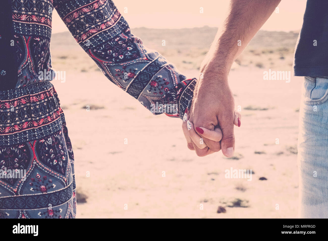 Close up de um par de mãos segurando tocando para real o verdadeiro amor entre mulher e homem caucasiano. juventude viajante em férias com praia destinat Imagens de Stock