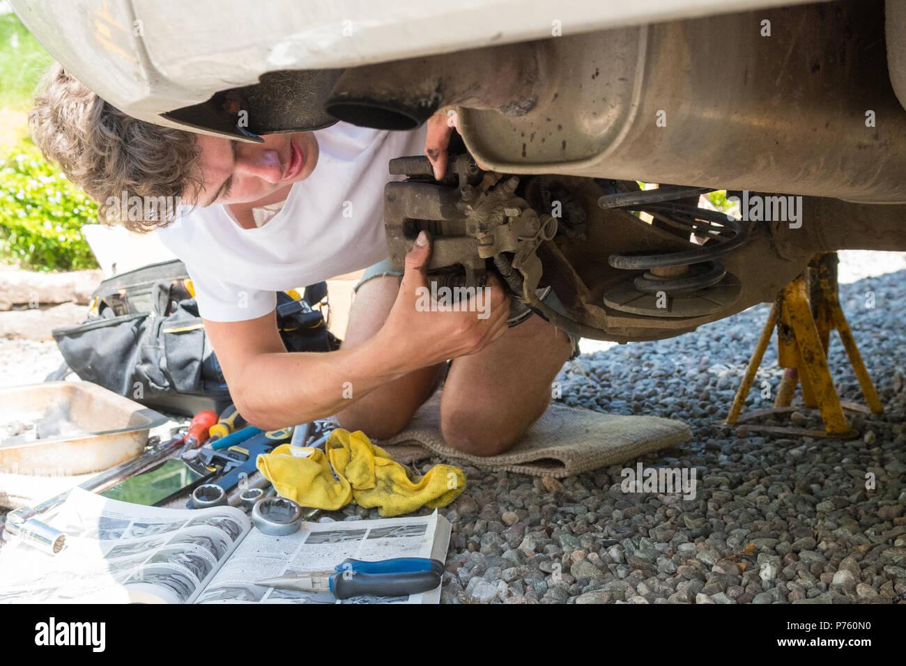 Jovem que fixa carro em casa removendo a pinça do freio como ele muda e as pastilhas de travão de disco Imagens de Stock