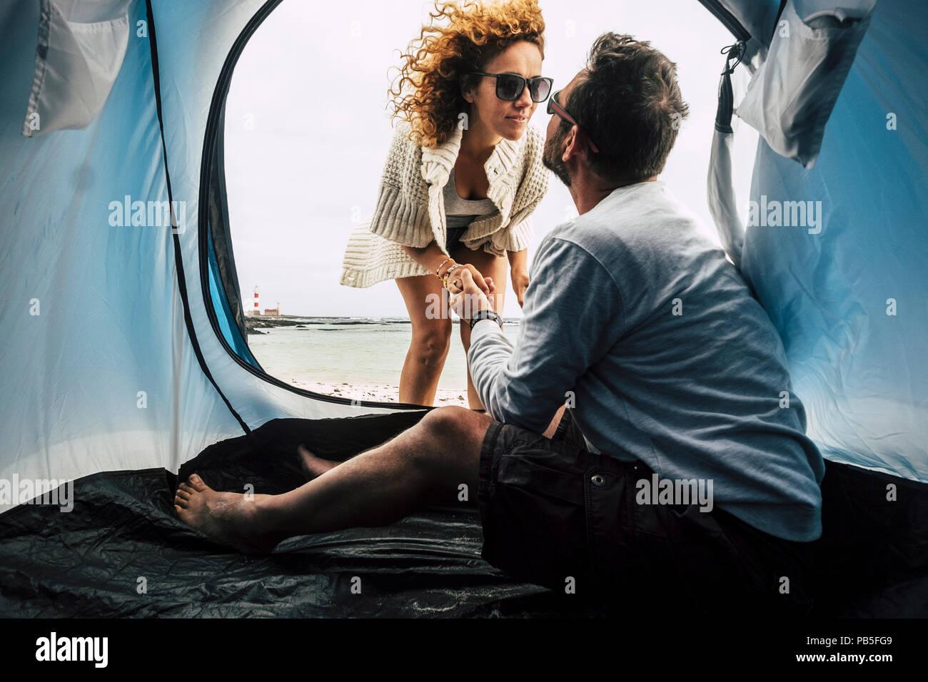 Dois homens e uma mulher branca, 40 anos de idade no amor camping na praia, em lugar tropical, que vivem perto do mar e desfrutar de suas férias na tenda. ki Imagens de Stock