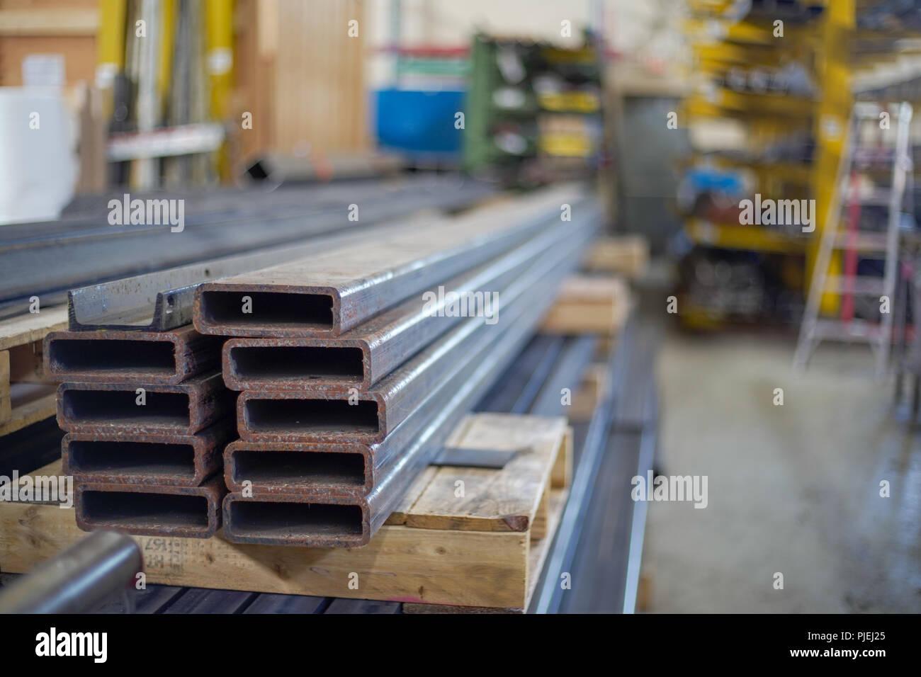 Tubos estruturais de aço empilhados sobre um skid, com racks de armazenamento de material e de fabrico em segundo plano Imagens de Stock