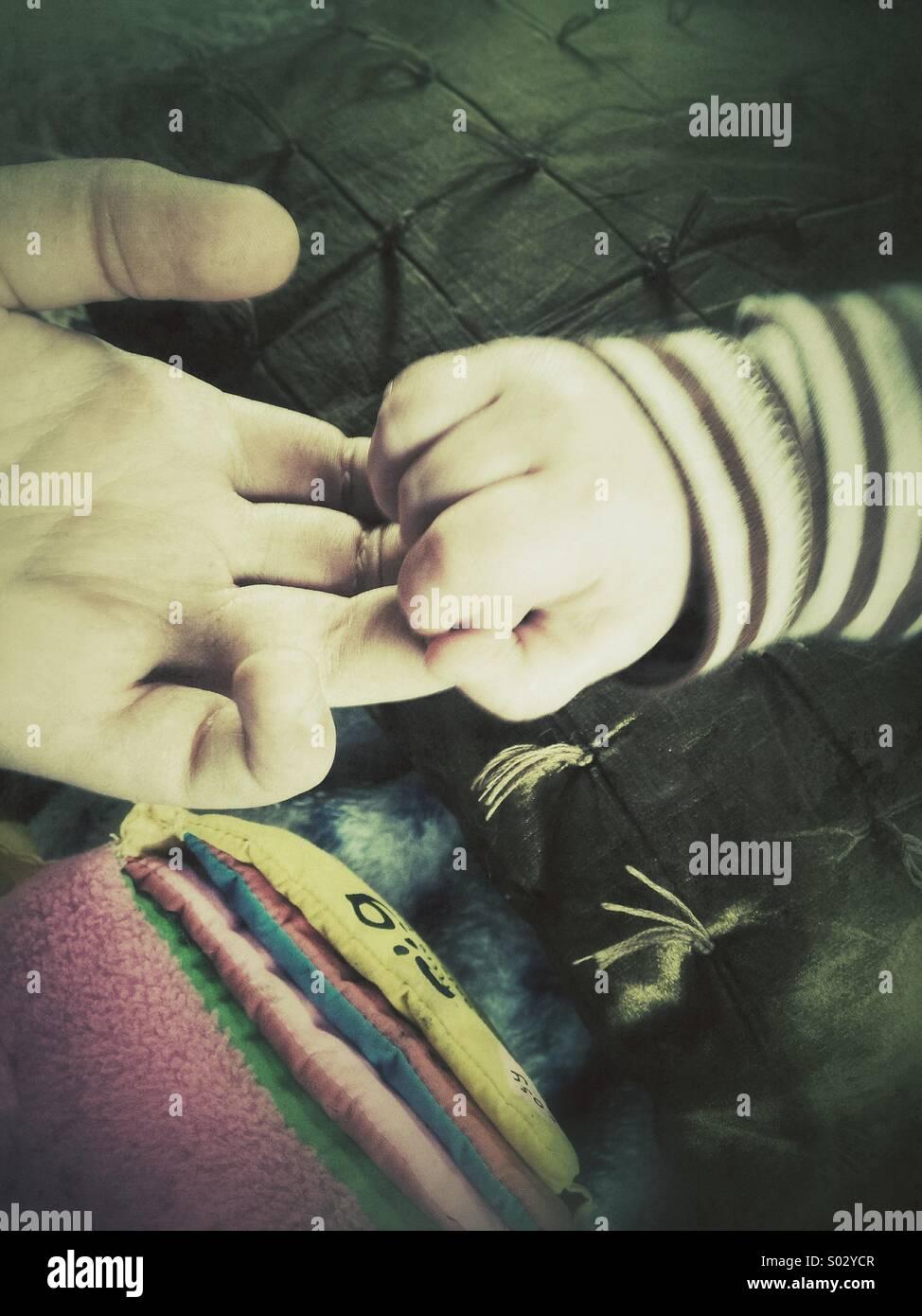 A infância, mãos do bebê segurando a mão do adolescente, filtro retro Imagens de Stock