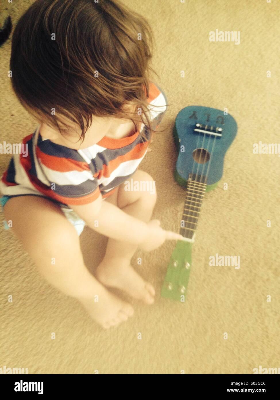Bebé com ukulele Imagens de Stock