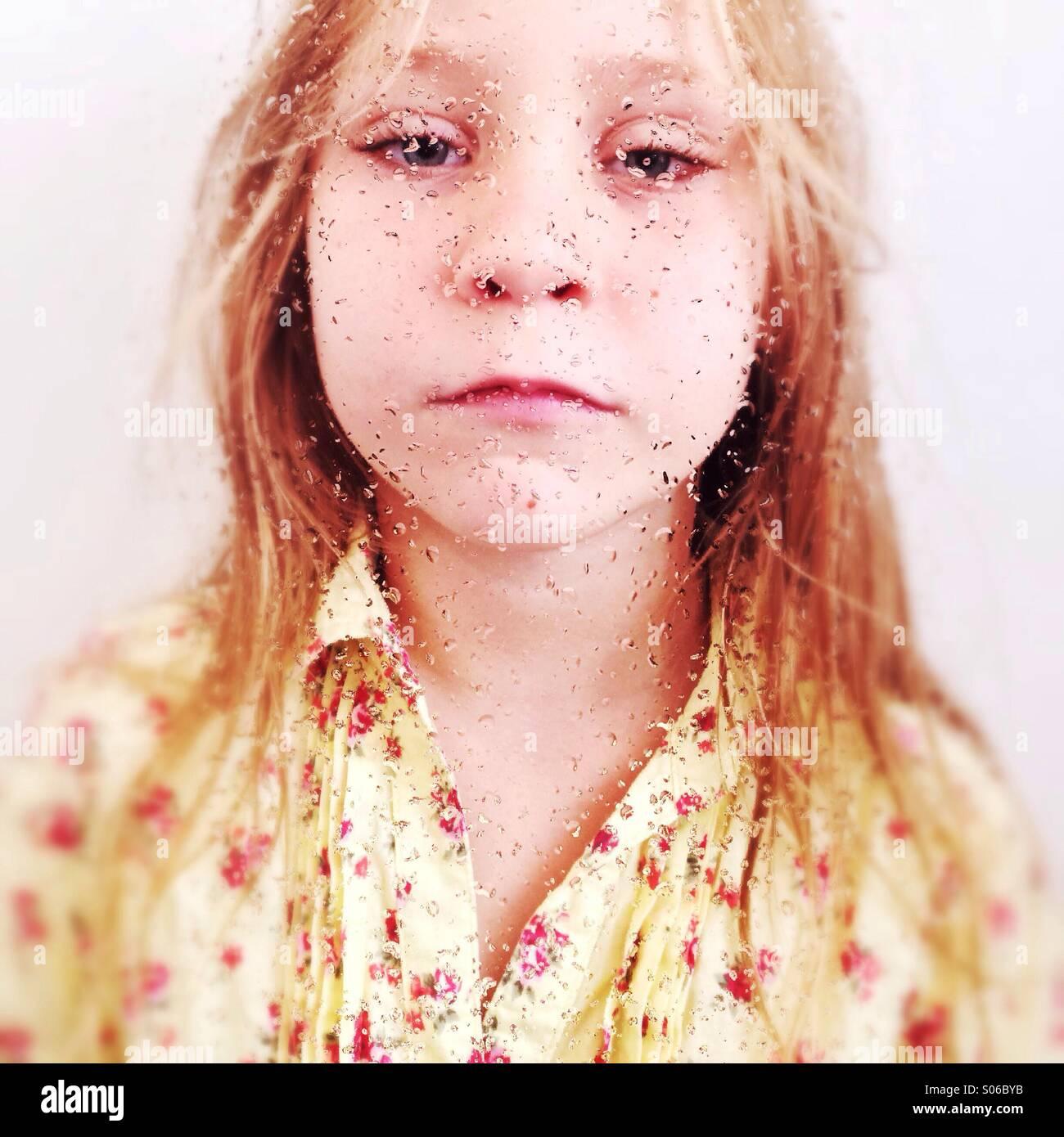 Retrato de uma jovem rapariga atrás de uma janela molhada. Imagens de Stock