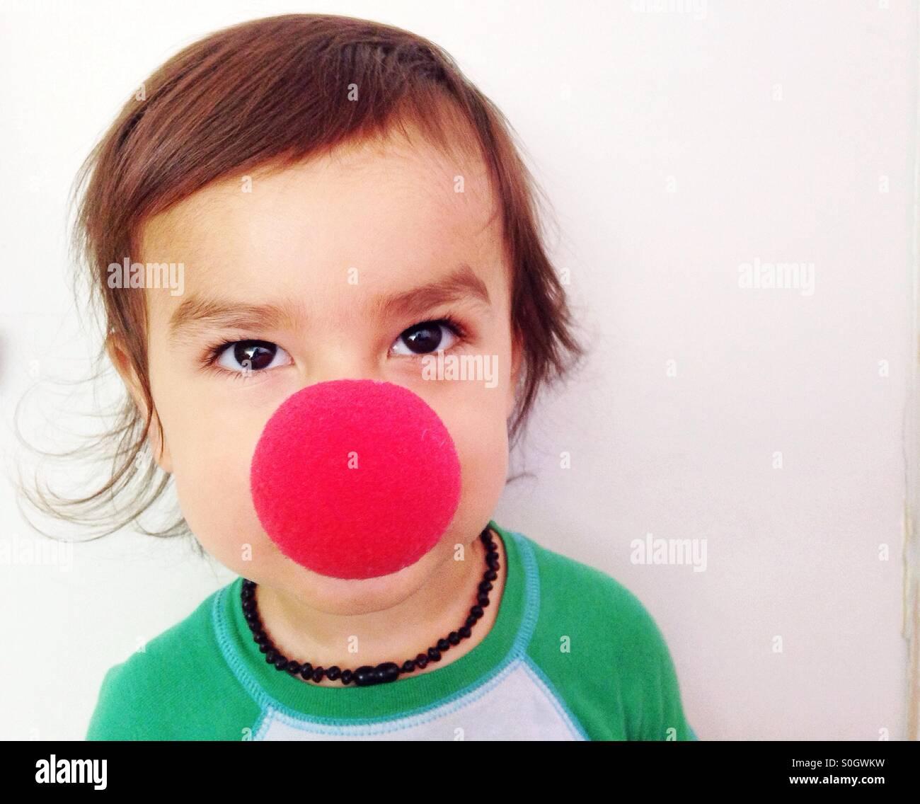 Bonitinha bebé com nariz vermelho de palhaço Imagens de Stock