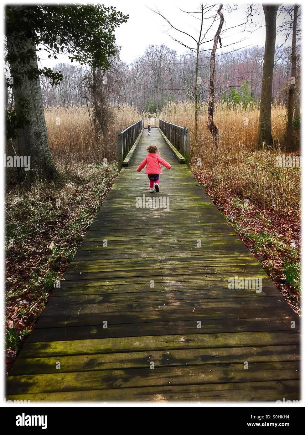 Toddler correndo ao longo de uma passarela no centro de natureza Imagens de Stock