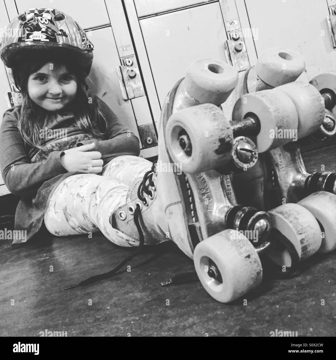 Toddler rapariga sentada vestindo patins. Imagens de Stock