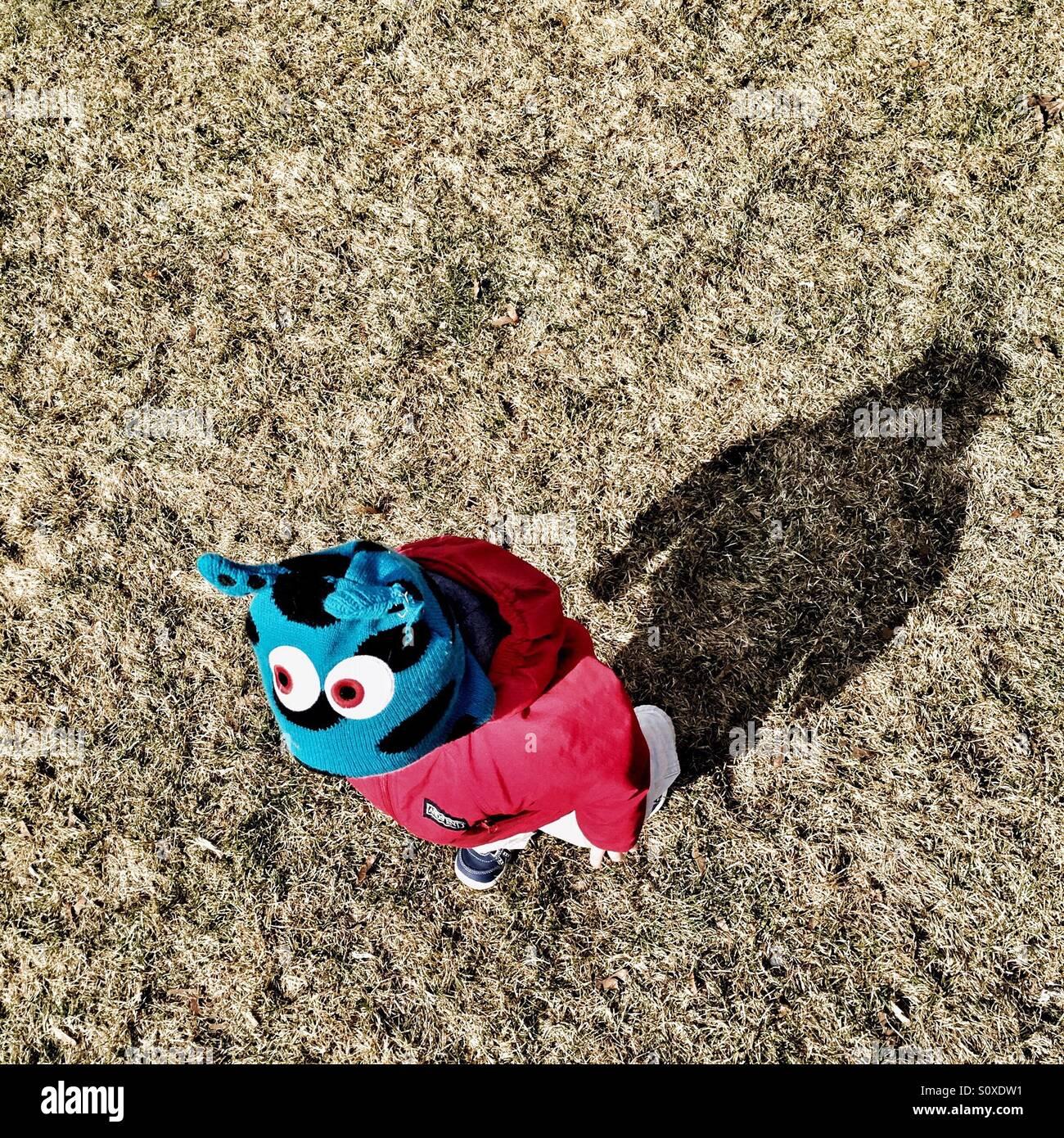 Toddler vestindo um monstro hat, seguido de sua sombra. Imagens de Stock