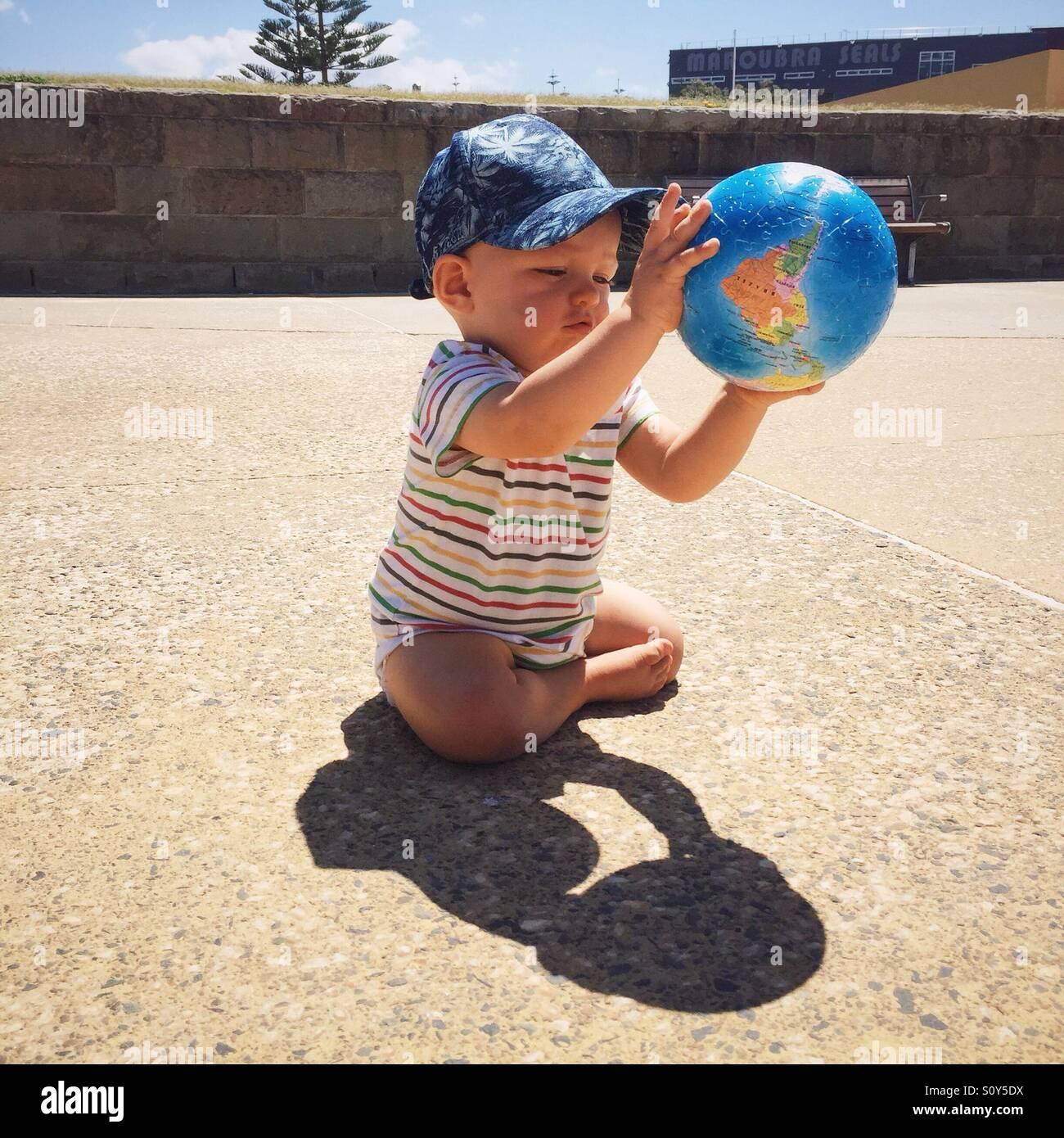 Criança que brinca com a bola globo Imagens de Stock