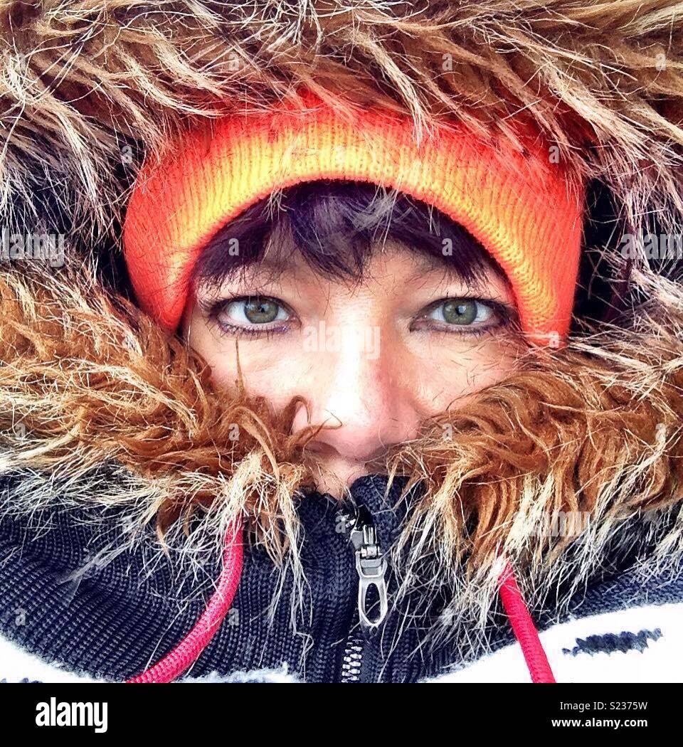 Mulher com capuz peludo e chapéu cor-de-laranja. Dispõe de esquimós. Nariz e olhos mostrando. Imagens de Stock