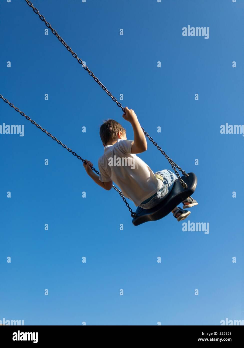 Menino voando alto em um balanço, conceito de memórias de infância Imagens de Stock