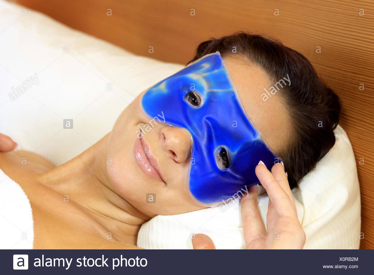 Junge Frau mit einer blauen Gelmaske, jovem mulher com uma máscara de gel azul, adulto, sozinho, bonito, beleza, brilhante, cuidado, branca Imagens de Stock