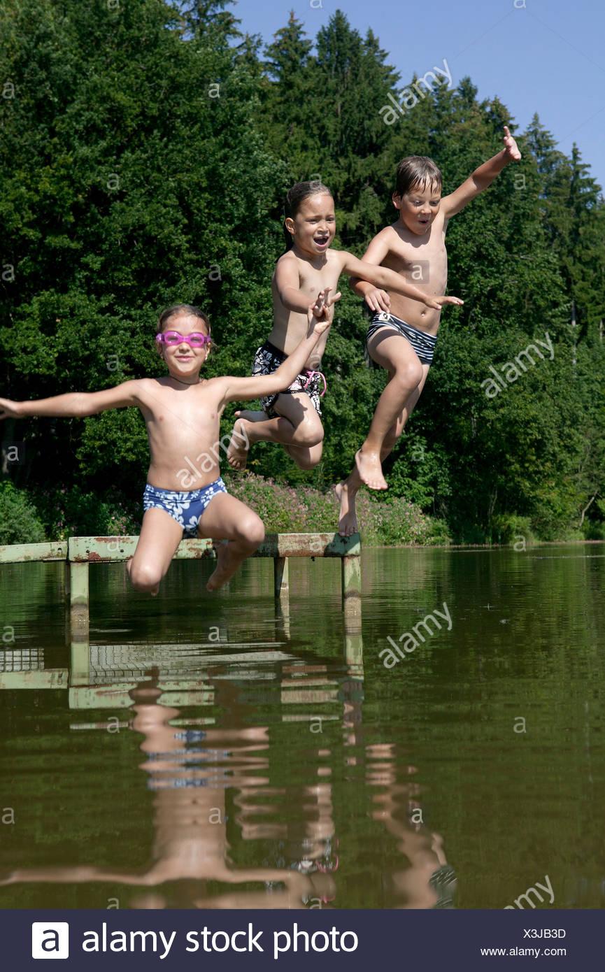 Três crianças saltar para o lago Imagens de Stock
