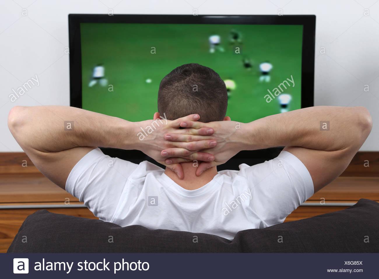 Junger Mann schaut Fußball im Fernsehen Imagens de Stock