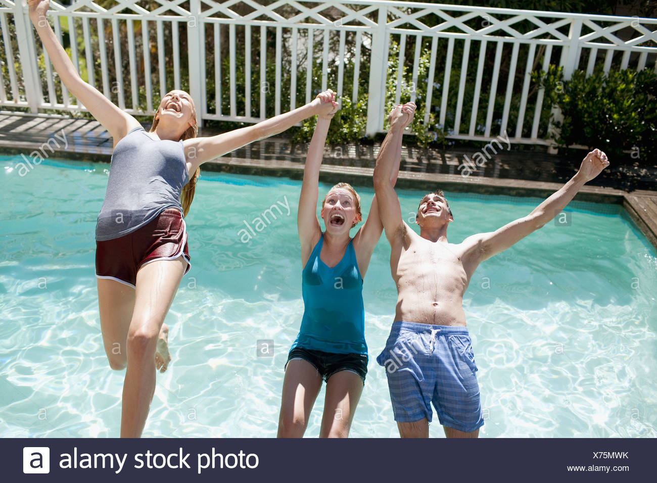 Friends holding hands and falling backwards into swimming